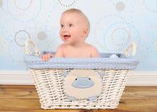 可爱的婴孩篮子穿蓝衣的男孩坐的柳条 库存照片