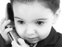 可爱的婴孩黑色男孩移动电话诉讼白色 免版税库存照片