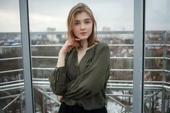 年轻可爱的学生白肤金发的青少年的女孩感人的头发获得在观察台的乐趣以多云春天天空为目的,结冰 免版税库存图片