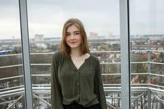 年轻可爱的学生白肤金发的青少年的女孩获得在观察台的乐趣以多云春天天空,结冰的河,晴朗的w为目的 库存图片