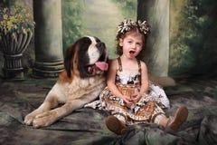 可爱的孩子和她的圣伯纳德小狗 免版税库存照片