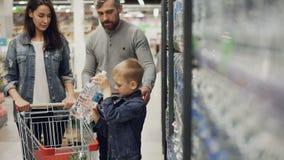 可爱的孩子在超级市场在购物车,他的慈爱的父母采取瓶从架子的水并且投入它 股票视频
