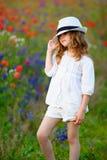 可爱的孩子女孩佩带的帽子在通过走热的夏日下 免版税库存图片