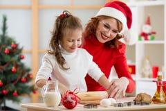 可爱的孩子女孩和母亲烘烤圣诞节曲奇饼 库存照片