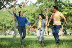 可爱的家庭获得乐趣在公园 免版税库存图片