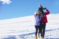 可爱的家庭获得乐趣在山的一个冬天公园 免版税库存照片