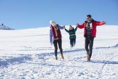 可爱的家庭获得乐趣在山的一个冬天公园 库存照片