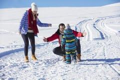 可爱的家庭获得乐趣在山的一个冬天公园 免版税库存图片