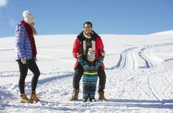 可爱的家庭获得乐趣在山的一个冬天公园 库存图片