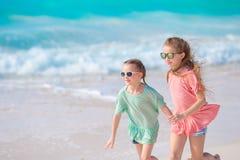 可爱的小女孩一起获得乐趣在白色热带海滩 库存图片