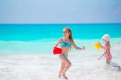 可爱的小女孩一起获得乐趣在白色热带海滩 库存照片