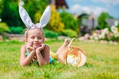 可爱的小女孩佩带的兔宝宝耳朵和篮子用复活节彩蛋 图库摄影