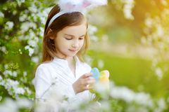 可爱的小女孩佩带的兔宝宝耳朵在开花的樱桃庭院里在春日 图库摄影