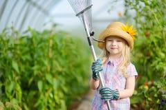 可爱的小女孩佩带的草帽和儿童的使用与她的玩具园艺工具的庭院手套自一间温室在夏日 免版税库存图片