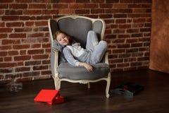 可爱的小女孩在与微笑的一把椅子斜倚在面孔 免版税库存图片
