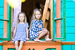 可爱的小女孩在农村房子窗口里  免版税库存图片
