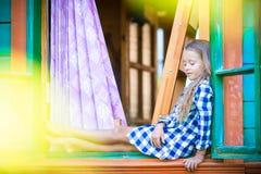 可爱的小女孩在农村房子窗口里  库存照片