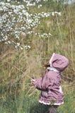 可爱的小女孩在开花的樱桃庭院里在美好的春日 免版税库存图片