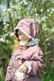 可爱的小女孩在开花的樱桃庭院里在美好的春日 免版税库存照片
