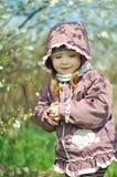 可爱的小女孩在开花的樱桃庭院里在美好的春日 库存照片