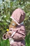可爱的小女孩在开花的樱桃庭院里在美好的春日 图库摄影