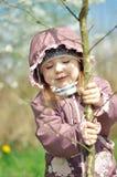 可爱的小女孩在开花的樱桃庭院里在美好的春日 库存图片
