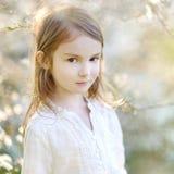 可爱的小女孩在开花的樱桃庭院里 库存图片