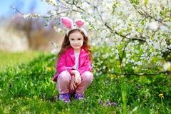 可爱的小女孩在开花的樱桃庭院里 免版税库存照片