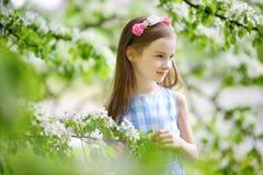 可爱的小女孩在开花的苹果树庭院里在春日 免版税库存照片