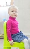 可爱的小女孩坐椅子 免版税库存照片