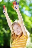可爱的小女孩用她的手绘了获得乐趣户外 免版税库存图片