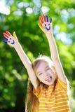 可爱的小女孩用她的手绘了获得乐趣户外 免版税图库摄影