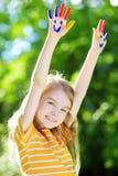 可爱的小女孩用她的手绘了获得乐趣户外 免版税库存照片