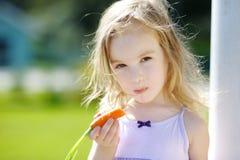 可爱的小女孩用红萝卜 图库摄影