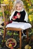 可爱的小女孩用苹果,秋天时间 库存图片