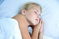 可爱的小女孩睡眠在床上 库存照片