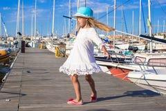 可爱的小女孩获得乐趣在一个口岸在夏天 免版税库存照片