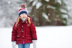可爱的小女孩获得乐趣在美丽的冬天公园 使用在雪的逗人喜爱的孩子 图库摄影