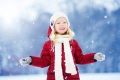 可爱的小女孩获得乐趣在美丽的冬天公园 使用在雪的逗人喜爱的孩子 免版税图库摄影