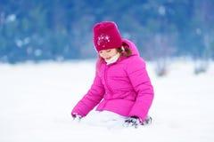 可爱的小女孩获得乐趣在美丽的冬天公园 使用在雪的逗人喜爱的孩子 库存照片