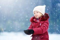 可爱的小女孩获得乐趣在美丽的冬天公园 使用在雪的逗人喜爱的孩子 免版税库存图片