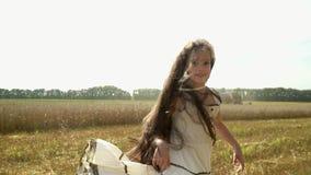 可爱的小女孩获得乐趣在金麦子的角色 深色头发的女孩在一件长的礼服被转动 慢的行动 影视素材