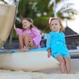 可爱的小女孩获得在白色海滩的乐趣 免版税库存图片