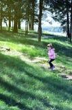 可爱的小女孩跑上木台阶在森林晴天 免版税库存图片