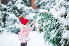 可爱的小女孩去的冰鞋在冬天雪天户外 免版税库存图片