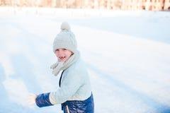 可爱的小女孩去的冰鞋在冬天雪天户外 库存图片
