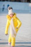 可爱的小女孩去的冰鞋在冬天雪天户外 库存照片