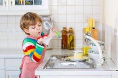 可爱的小孩儿童洗涤的盘在国内厨房里 免版税库存照片
