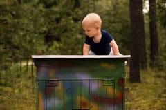 可爱的小孩坐五颜六色的箱子反对被弄脏的自然背景 屋顶的逗人喜爱的男婴 免版税库存图片