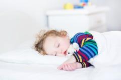 可爱的小孩女孩在一张白色床上的采取休息 免版税库存图片